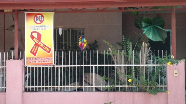Anti-RH Bill poster shown in front of a house of a pro-life family.