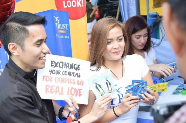 "A seminarian showing the ""Exchange Your Condoms for Candies and Real Love"" sign. Beside him is a lady distributing condoms."